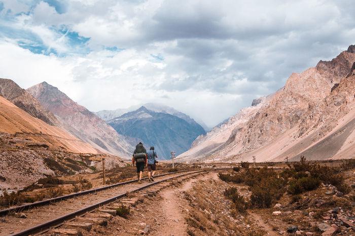 Rear view of people walking on railroad