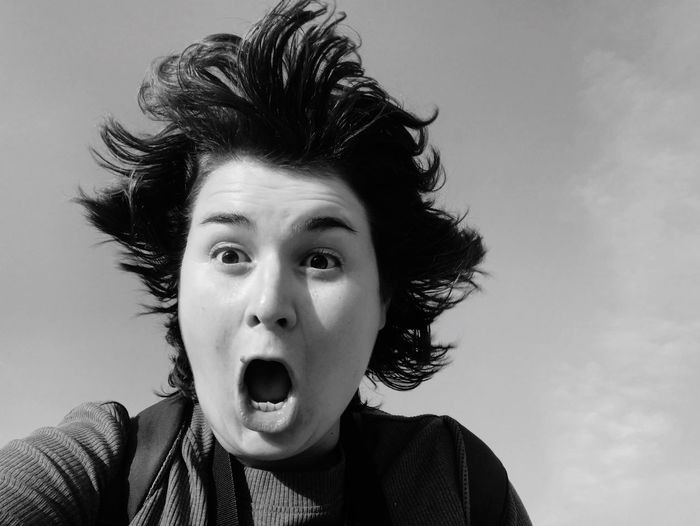 Close-up of woman screaming against sky
