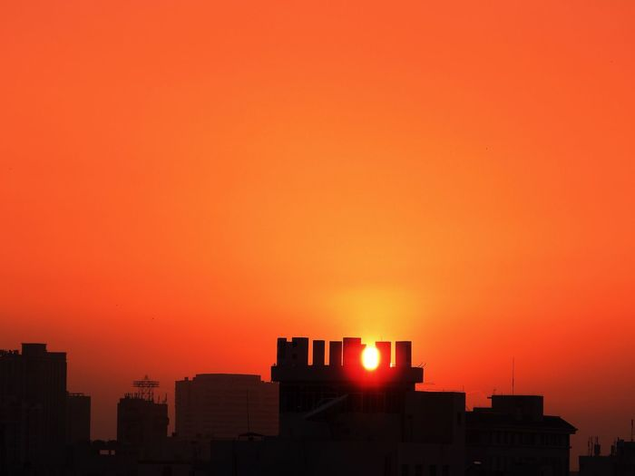 Silhouette Buildings Against Orange Sky