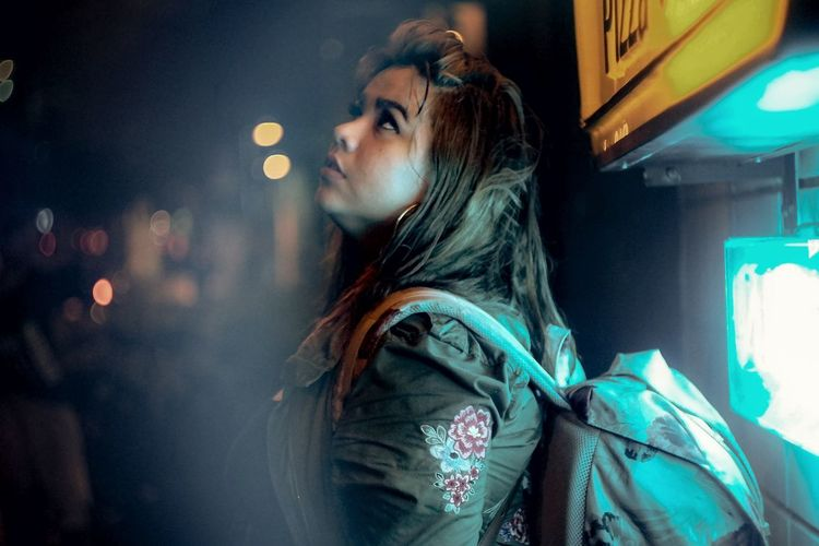 Portrait of young woman looking away at night