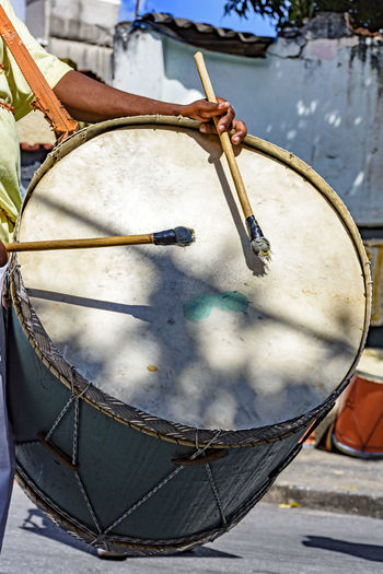 Midsection of man playing drum with sticks