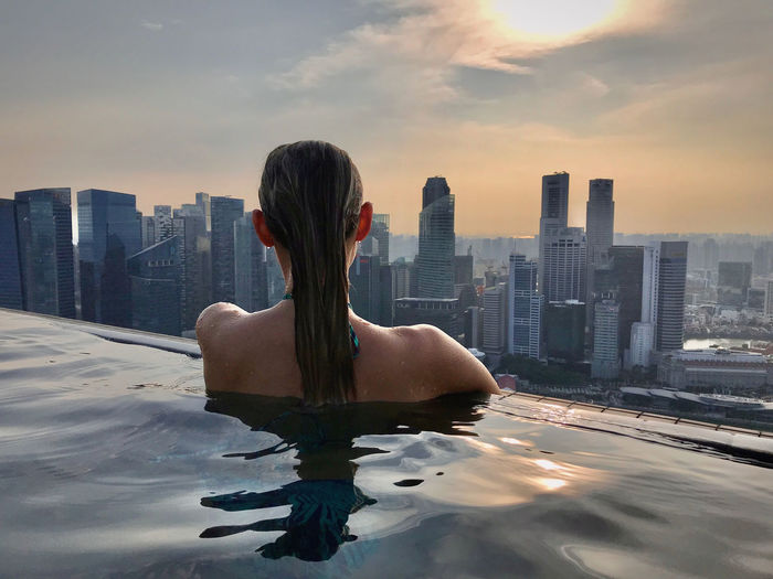 Rear view of woman in swimming pool against buildings in city