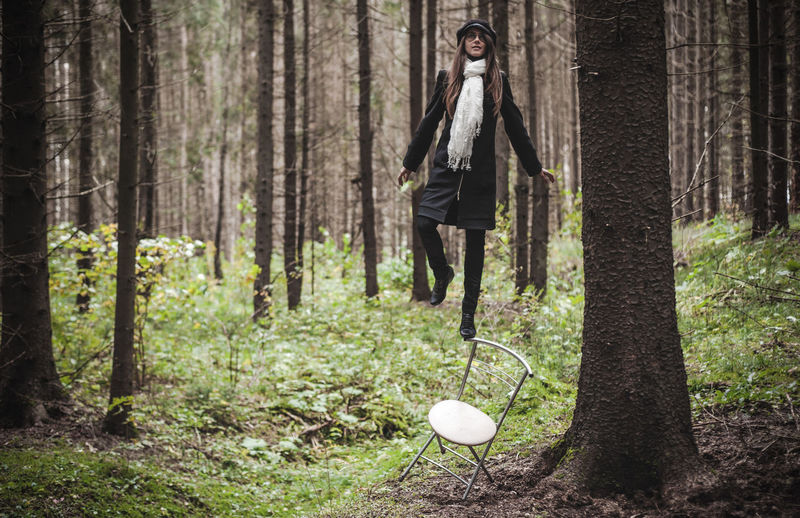 Woman Balancing On Chair Against Trees In Forest