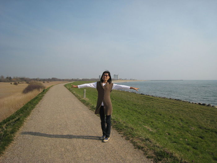 Full length of woman with arms outstretched standing on footpath at beach