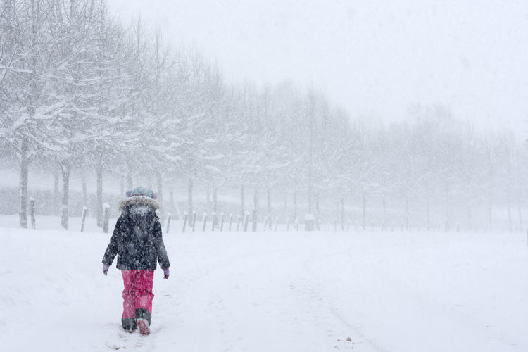 Rear view of girl walking on snow covered landscape