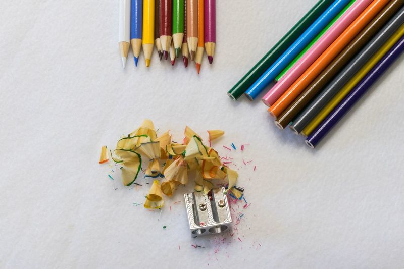 Sharp as a Pencil Multi Colored Colored Pencil Pencil Still Life Variation Large Group Of Objects Pencil Shavings Art And Craft High Angle View Wood - Material Pencil Sharpener No People Table Indoors  Variety Choice Paper Close-up