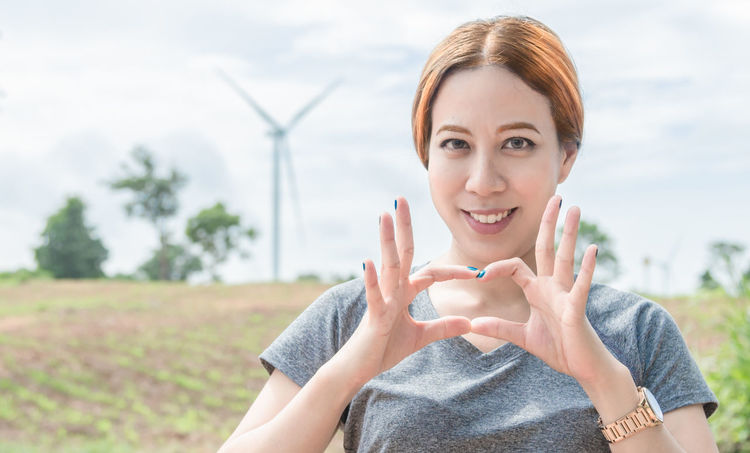 Portrait of cute woman with wind turbine background Alternative Energy Day Focus On Foreground Headshot Lifestyles Nature One Person One Woman Only One Young Woman Only Outdoors People Portrait Renewable Energy Sky Smiling Wind Power Wind Turbine Windmill Young Adult Young Women