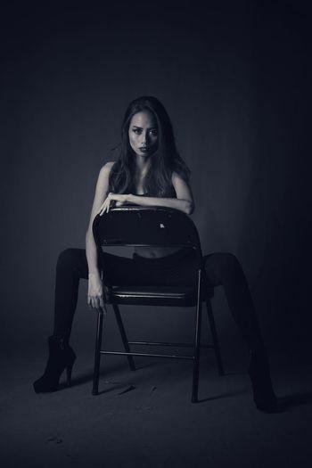 Portrait of beautiful fashion model sitting on folding chair against black background