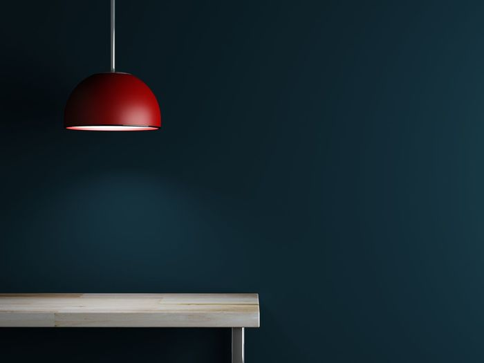 Illuminated Red Pendant Light Hanging Over Wooden Table By Blue Wall