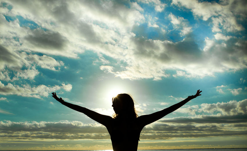Rear view of woman with arms outstretched against cloudy sky