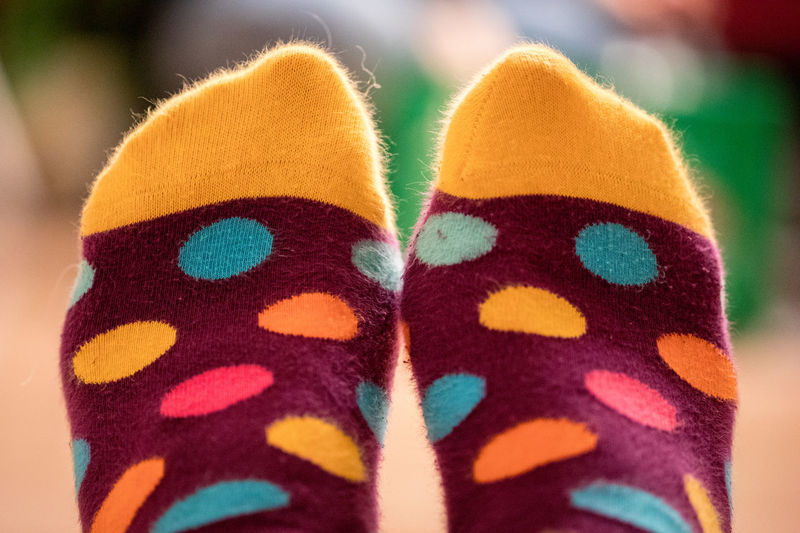 Low section of person wearing colorful spotted socks