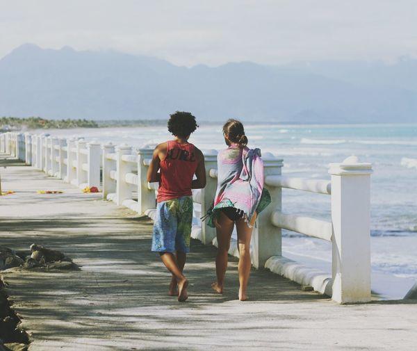 Rear view of people walking on beach against sky
