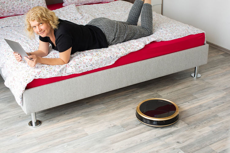 High angle portrait of woman using digital tablet while lying on bed by vacuum cleaner