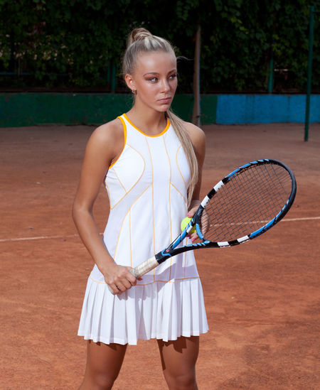 Beautiful young woman in a tennis dress and with the racket in her hand standing on a sandy court Racket One Person Tennis Racket Three Quarter Length Standing Sport Tennis Holding Leisure Activity Women Lifestyles Real People Clothing Young Adult Front View Day Playing Young Women Outdoors Beautiful Woman Hairstyle