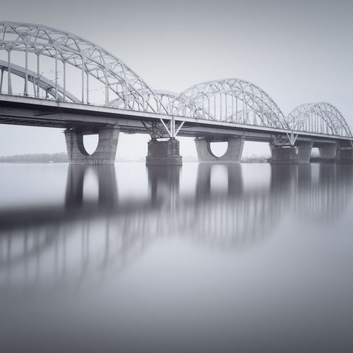 Low angle view of bridge against clear sky Architecture Bridge - Man Made Structure Built Structure Clear Sky Connection Day Engineering Fine Art Kiev Long Exposure Low Angle View Muted Colors New Darnytskyi Bridge No People Outdoors Philipp Dase Railroad Bridge River Sky Transportation Ukraine Water Winter