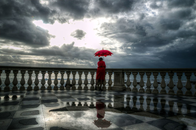 Waiting the return Cloud - Sky Sea Full Length Water Sky One Person Storm Cloud Outdoors Beach Beauty In Nature Dream Eyem Vision Gildo Masini Live Light Tuscany Colors Red Umbrella Umbrella Italia Sunlight ☀ Real People One Woman Only Street Light