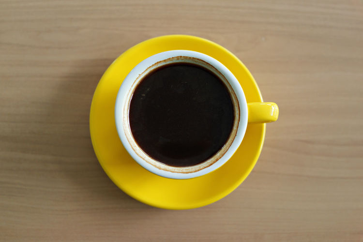Hot black coffee on desk Drink Cup Food And Drink Refreshment Mug Directly Above Table Coffee Cup Coffee - Drink Coffee Freshness Yellow Crockery Saucer Black Coffee High Angle View Still Life No People Close-up Hot Drink Black Tea Tea Cup Non-alcoholic Beverage Wood Grain Americano