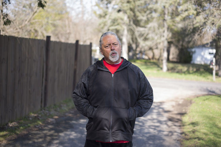 Portrait Of Senior Man Making Face While Standing On Footpath At Park