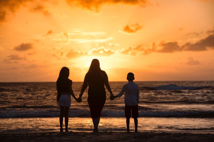 Rear View Of Mother With Son And Daughter Standing At Beach Against Sky During Sunset