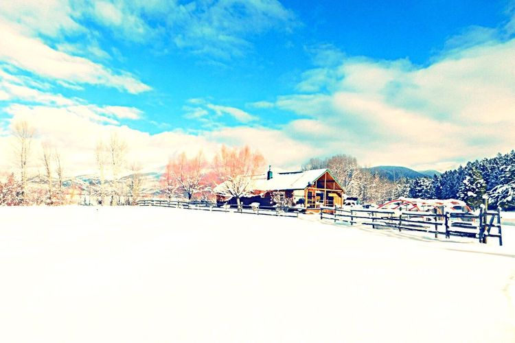 Snow covered landscape and houses against sky