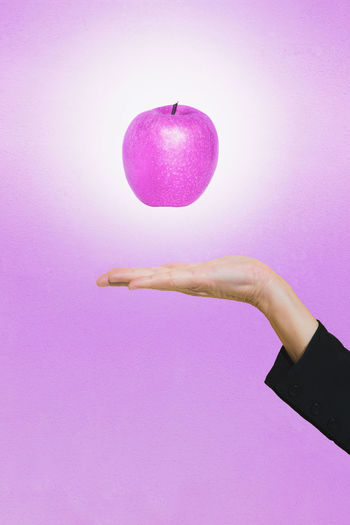 Close-up of hand with levitating apple against pink background