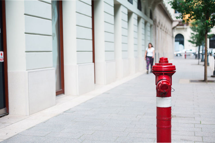 Fire Hydrant On Sidewalk Against Woman Walking In Background