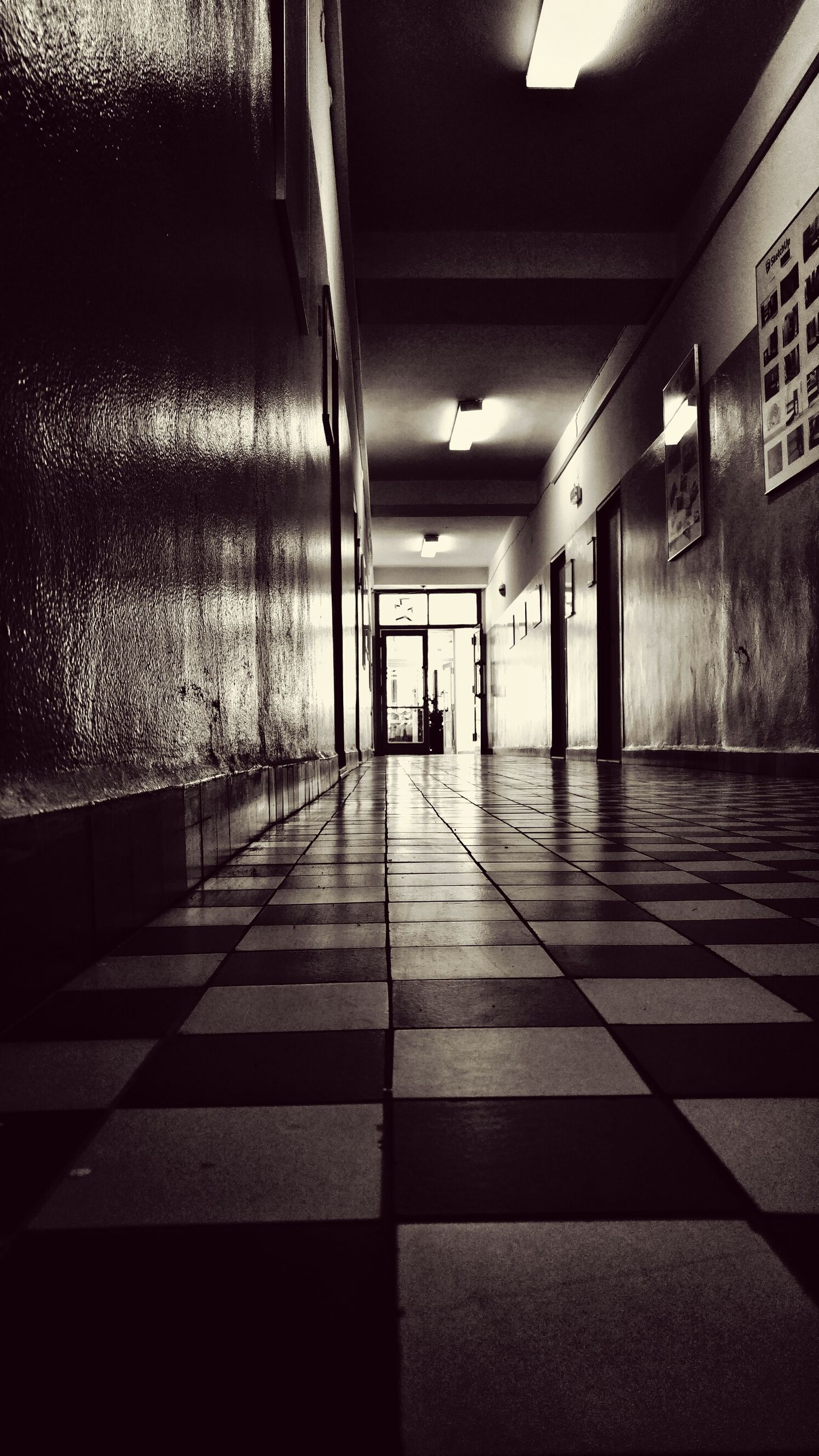 indoors, architecture, built structure, the way forward, corridor, ceiling, empty, illuminated, flooring, tiled floor, lighting equipment, diminishing perspective, door, absence, building, architectural column, wall - building feature, window, walkway, no people