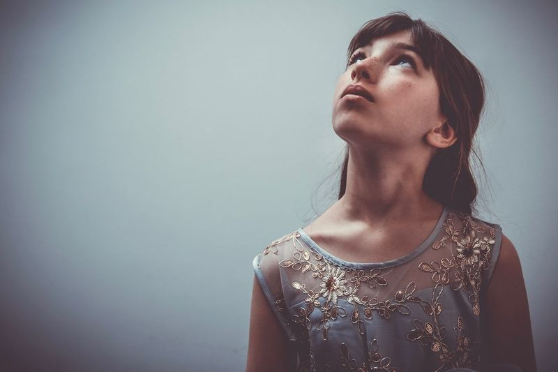 Portrait of a young woman looking away against wall