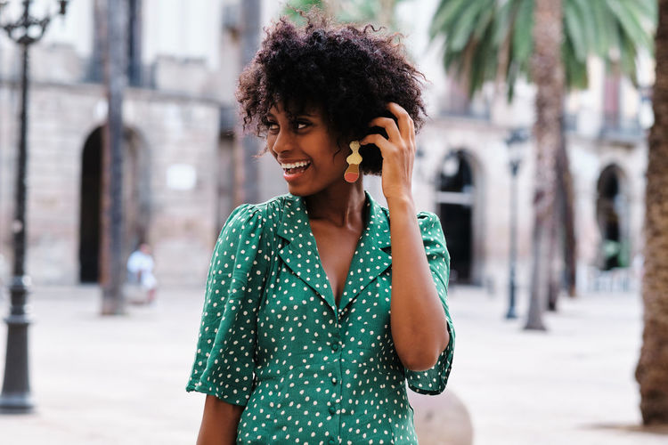Smiling young woman using smart phone in city