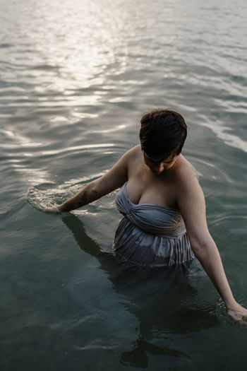 pregnant woman sitting in sea