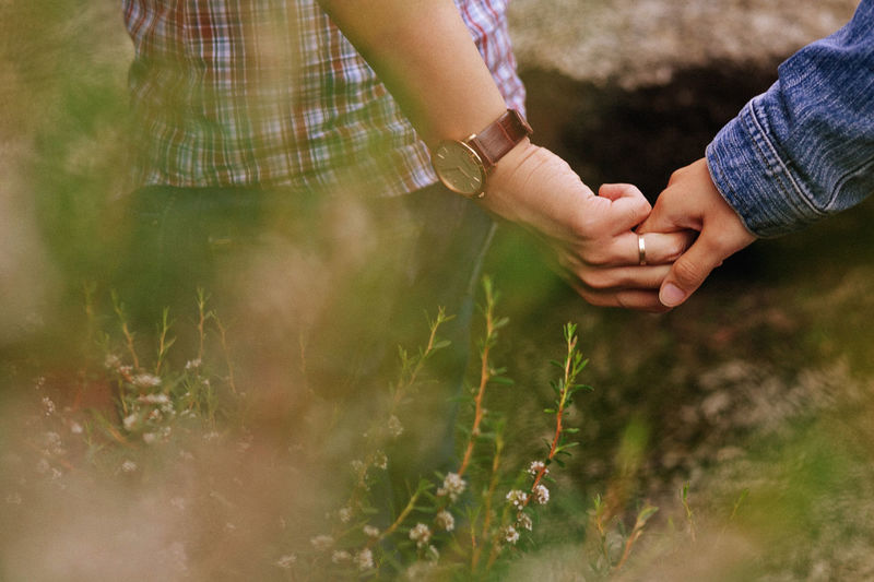 Cropped couple holding hands on field