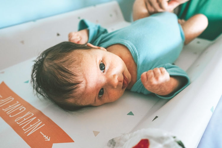 High angle portrait of baby lying on table at home