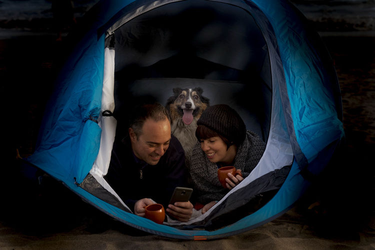 Couple with dog using mobile phone in tent at night