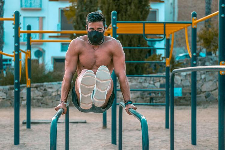 Shirtless man wearing mask exercising at park