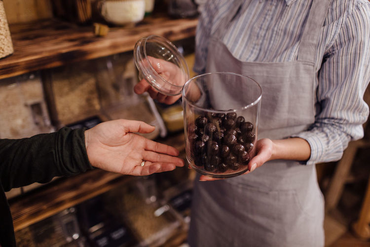 Shop assistant holding glass jar with healthy chocolate balls in organic store. Zero waste shopping - hand of customer pointing at fresh sweets in package free food store. Zero Waste Plastic Free Package Shop Store Raw Food Food Refill Organic Shopping Business Homemade Horizontal Grocery Bulk Interior Customer  Assistant Shopkeeper Two People Chocolate Hand Bio Eco