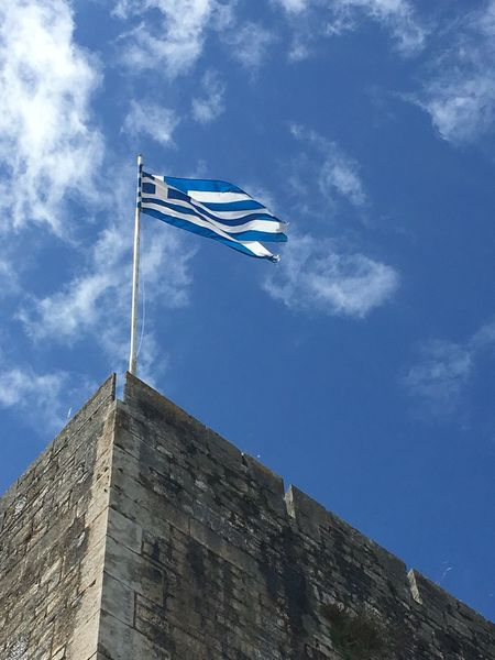 Greek flag flying in the wind atop the New Fortress, Corfu Town, Greece Ancient Ruins Architecture Blue Blue Skies Cloud Cloud - Sky Cloudy Corfu Town Day Flag Pole Flying In The Wind Greek Flag Looking Up Low Angle View New Fortre New Fortress No People Outdoors Sky Tall - High