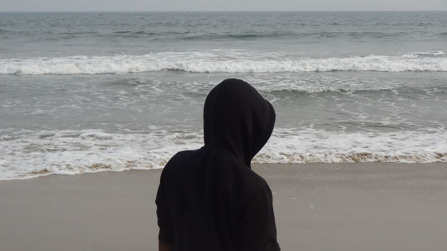 Rear view of person wearing hooded shirt against sea at beach
