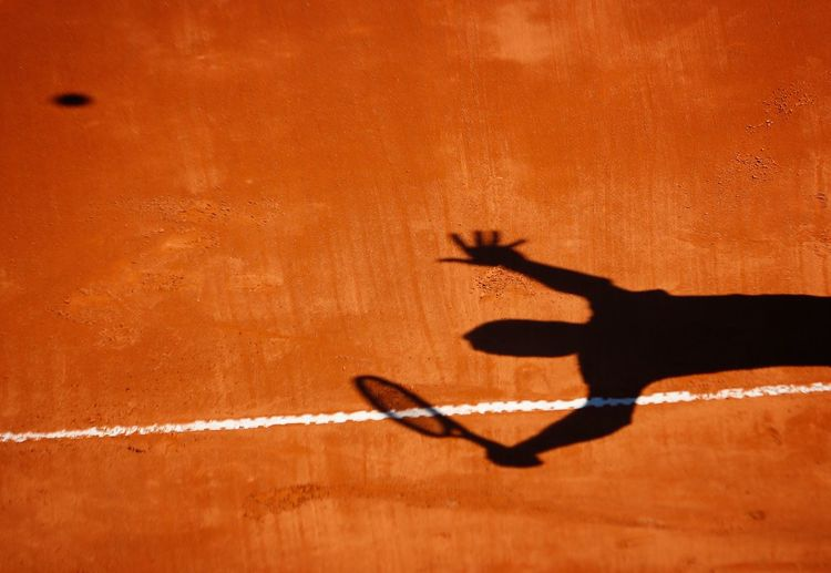 Shadow on man playing tennis on field