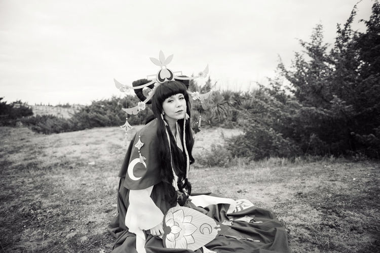 Portrait of young woman wearing cosplay costume sitting on field