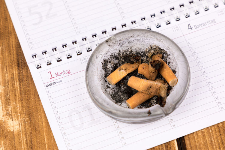 High Angle View Of Ashtray On Paper