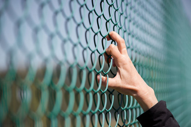 Adult Adults Only Baseball - Sport Baseball Helmet Broken Dreams Chainlink Fence Close-up Day Depressed Fingers Human Body Part Human Hand Metal Fence One Person Outdoors People Playing Field Prison Prisoner Real People Refugees Sport Stress Team Sport Woman Fingers
