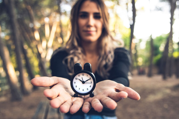 Close-up of woman holding clock against trees