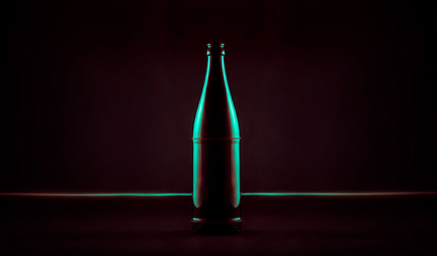 Close-up of illuminated bottle against black background