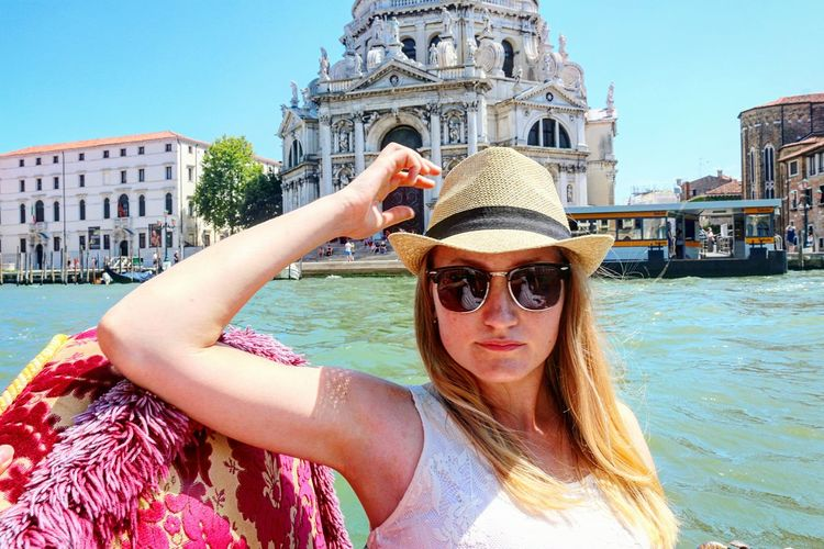 Woman wearing sunglasses in gondola on grand canal