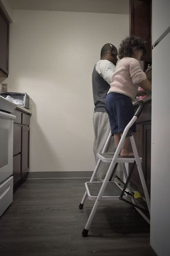 Father and daughter cleaning up dishes together in kitchen