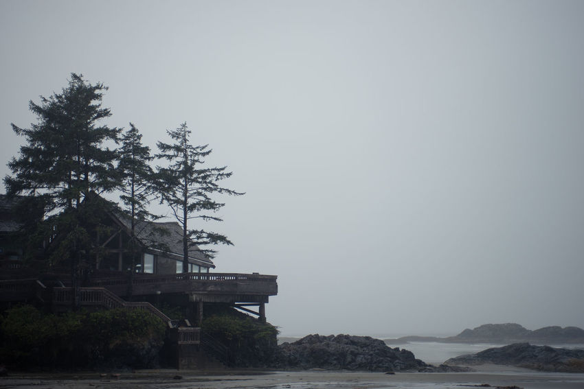 a building overlooks Wickaninnish Beach in Tofino British Columbia. Architecture Beautiful BC Beauty In Nature British Columbia Building Exterior Built Structure Clear Sky Day Mist Nature No People Ocean Outdoors Pacific Ocean Pacific Rim National Park PNW Scenics Sea Sky Tofino Tranquility Tree Vista Water West Coast