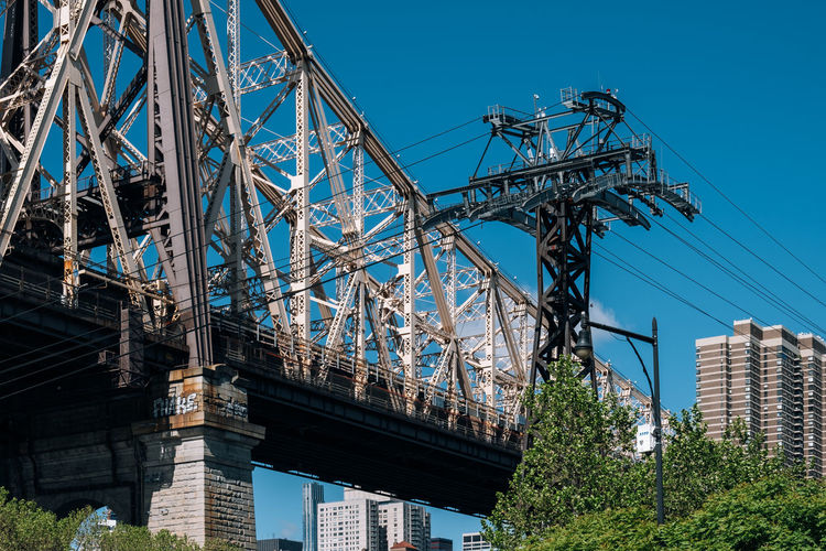New York City - USA - May 15 2019: Queensboro bridge and tramway of Manhattan midtown from Roosevelt Island East River Landscape America Architecture Blue Bridge Building Cable City Cityscape Day Downtown East Famous Garden Island Landmark Lifestyle Manhattan Midtown Modern New New York City NY NYC Panoramic Park Queensboro River Roosevelt Roosevelt Island Scenic Sky Skyline Skyscraper Spring Street Sunny Tourism Tower Tram Tramway Transportation Travel Urban USA View Water Waterfront York