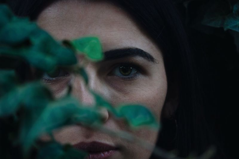 Close-Up Of Woman By Plant