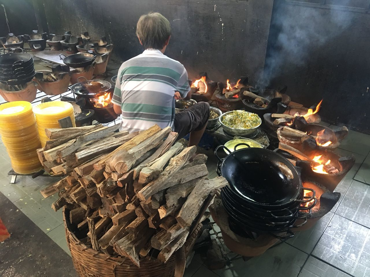 heat - temperature, real people, burning, fire, fire - natural phenomenon, flame, one person, men, preparation, food, food and drink, glowing, nature, smoke - physical structure, high angle view, container, rear view, log, firewood, preparing food