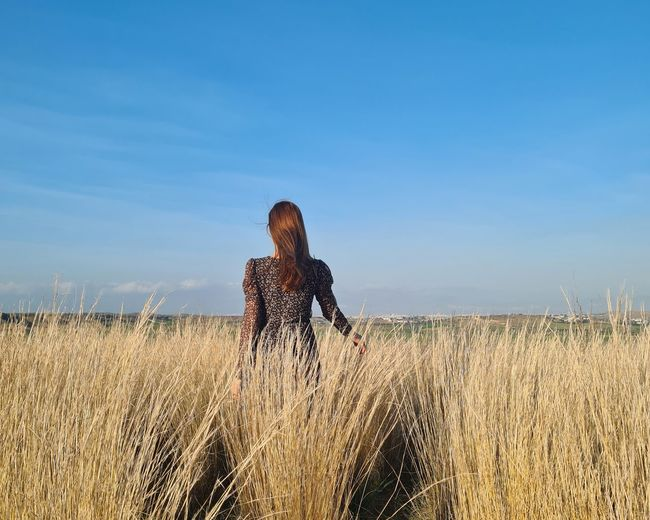 Rear view of woman standing on field against sky